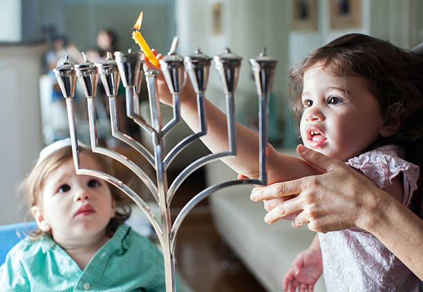 Young girl lights the Hanukkah menorah with help from adult Lighting  the Hanukkah Menorah judaism stock pictures, royalty-free photos & images