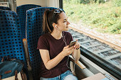 A young girl listens to a music or podcast while traveling in a train