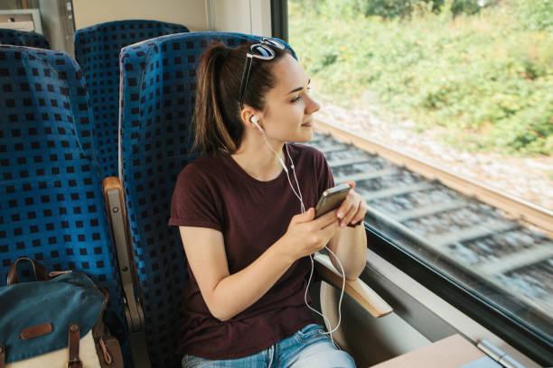une jeune fille écoute une musique ou un podcast tout en voyageant dans un train - train photos et images de collection