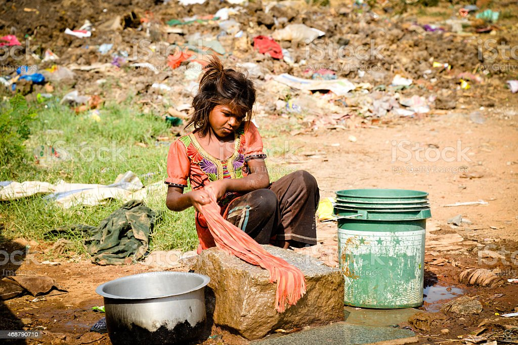 A Young Girl Living In Poverty Washing Clothes In A Bucket -7626