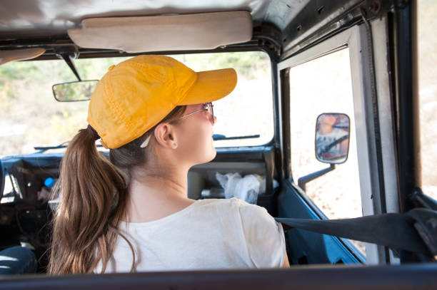 young girl looking around in jeep car during safari travel. - wildlife conservation stock photos and pictures