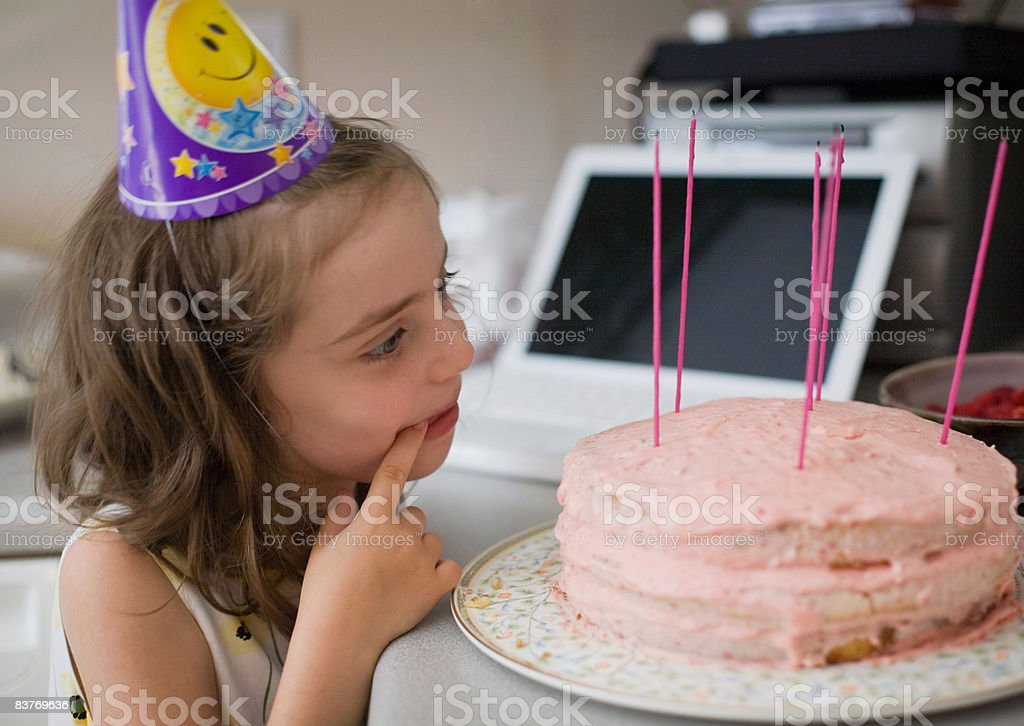 Young girl looking at birthday cake on counter royaltyfri bildbanksbilder