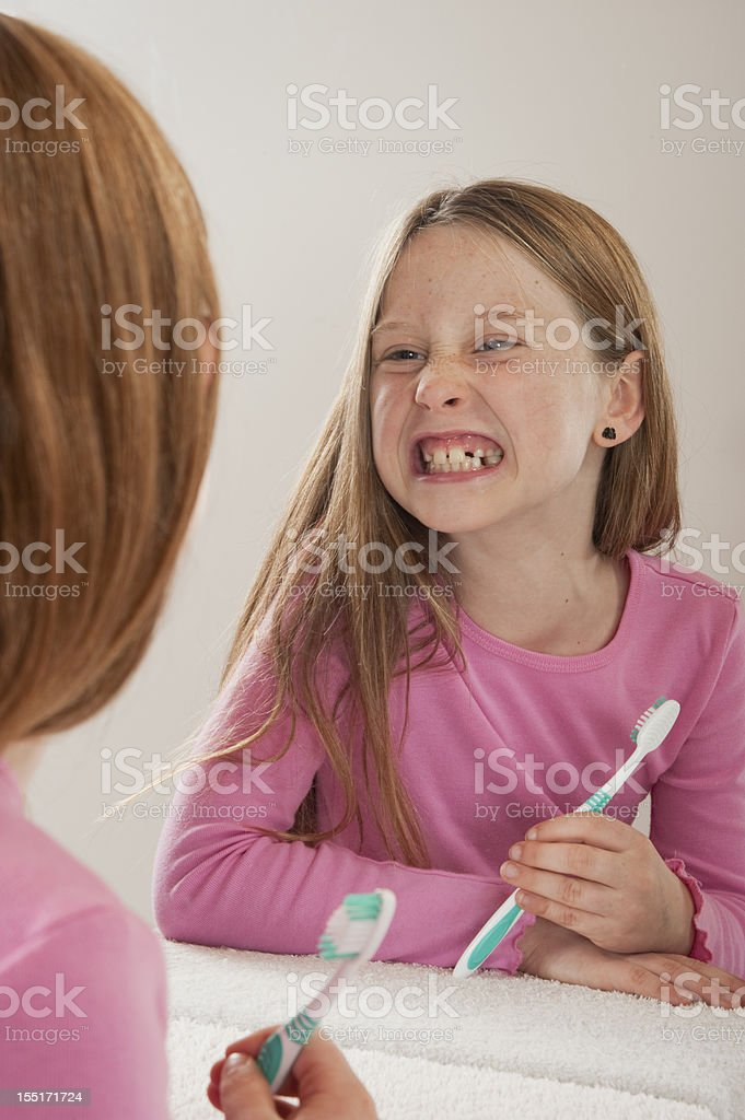 young girl looking at herself in mirror while brushing teeth royalty-free stock photo