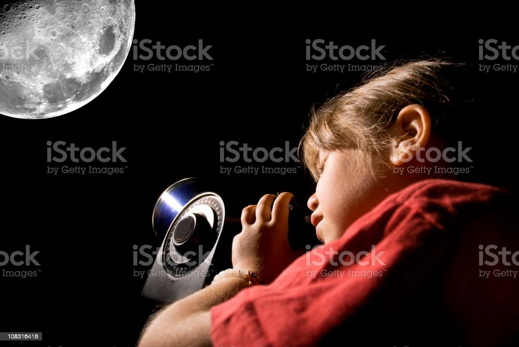 Young girl looking at the moon through an electronic telescope stock photo