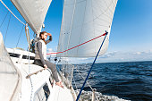 Young lady looking forward having trip on sailing yacht at a speed swimming in wind through blue sea. Outdoors horizontal colored image. Vide angle view.