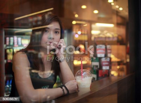 istock Young girl looking out behind the cafe window 506066281