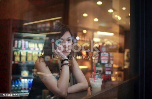 istock Young girl looking out behind the cafe window 506332571