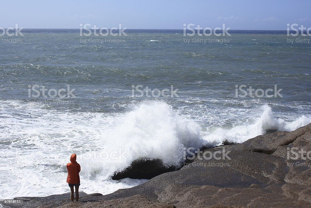 Young girl looking out over a rough ocean royalty-free stock photo