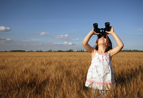 A young girl looking through binoculars outside