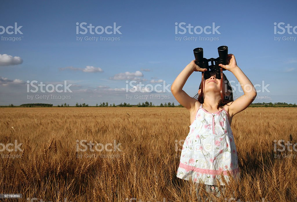 A young girl looking through binoculars outside stock photo
