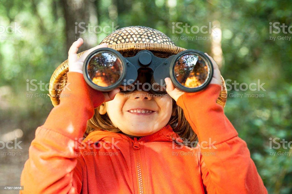 Young girl looking through binoculars stock photo