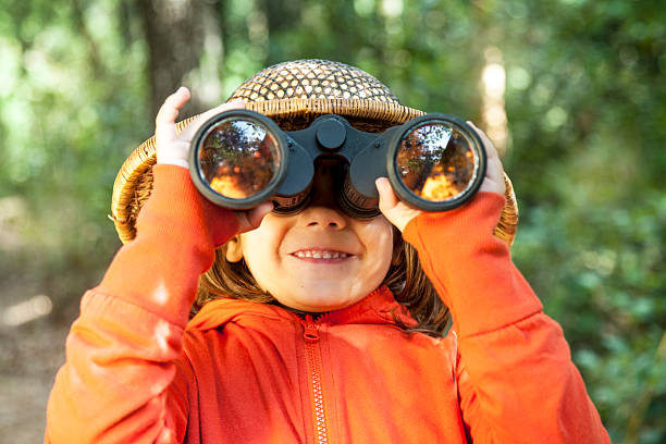Young girl looking through binoculars stock photo