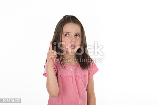 istock Young girl looking up and pointing her finger up as if she found an answer, solutions or have an idea. Isolated on a white background. Copy space 917926122