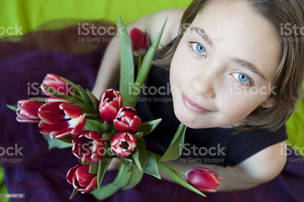 Young girl looking up with a tulip bouquet in hands. royalty-free stock photo