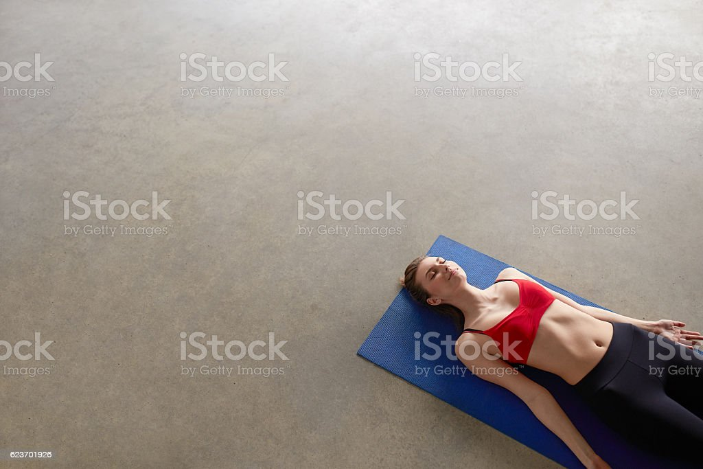 young girl lying down asana Savasana. stock photo