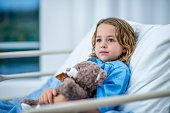 A girl of elementary age lies in a hospital bed and looks across the room with a noble, innocent expression. She is holding a teddy bear in her arms and wearing blue hospital clothing.
