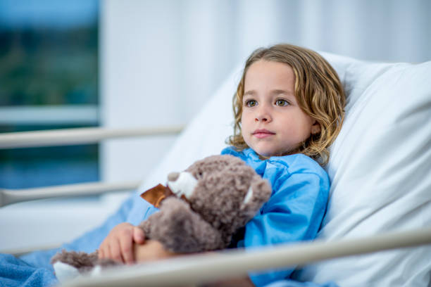 Young girl lying in a hospital bed looking stoic A girl of elementary age lies in a hospital bed and looks across the room with a noble, innocent expression. She is holding a teddy bear in her arms and wearing blue hospital clothing. sentimentality stock pictures, royalty-free photos & images