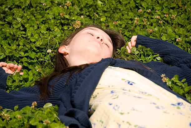 Young girl lying in clover stock photo