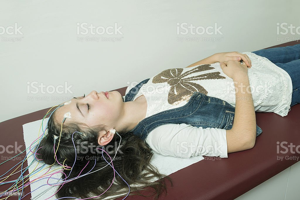 A young girl lying on a bed and having a EEG exam royalty-free stock photo