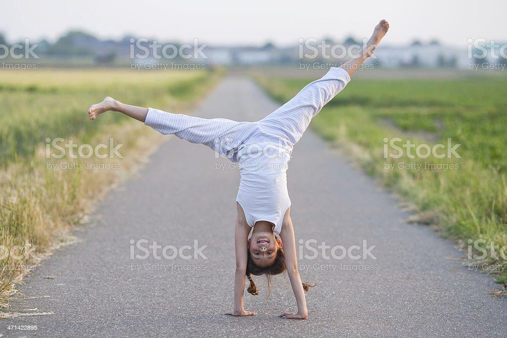 young girl makes a cartwheel stock photo