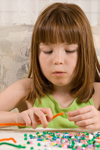 Young girl making a bead bracelet stock photo