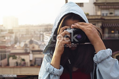 young girl making a photo with a vintage camera, on a terrace of Barcelona at sunset