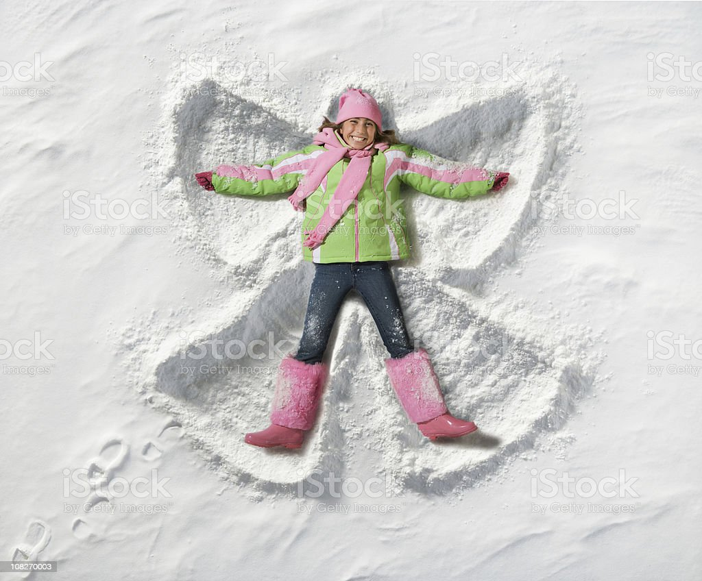 young girl making a snow angel royalty-free stock photo