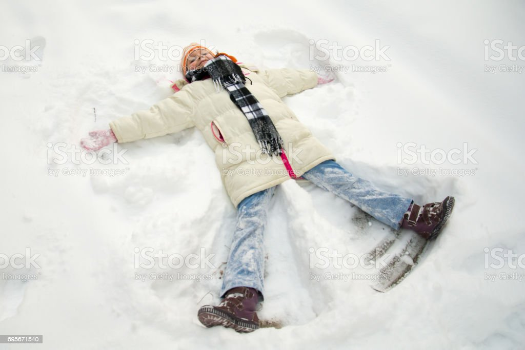 Young girl making a snow angel stock photo