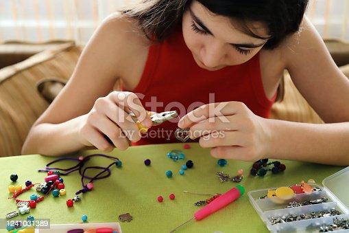Young girl making bead bracelets at home