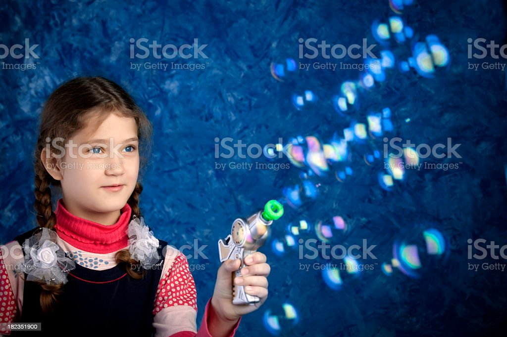 Young girl making blow bubbles with soap pistol stock photo