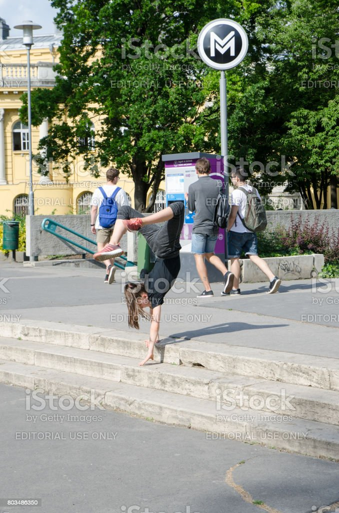 Young girl making gymnastic by going down stairs walking on hands stock photo