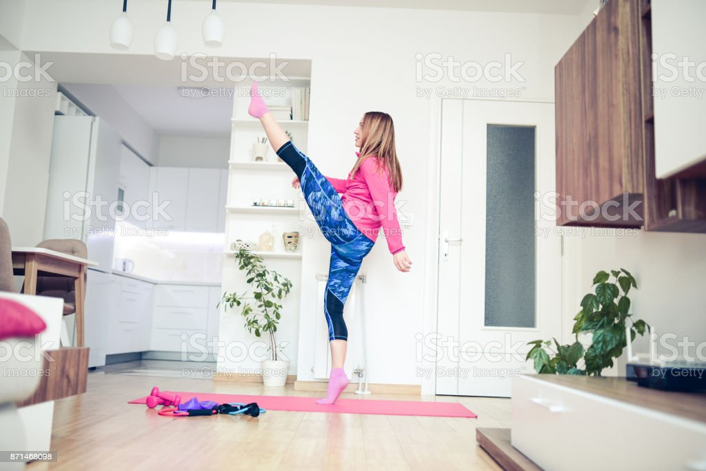 Young Girl Making Kick Box Fitness Exercise In the Living Room