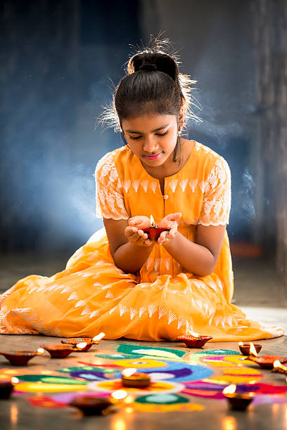 young girl making rangoli, decorating with oil lamps for diwali - ディワリ ストックフォトと画像