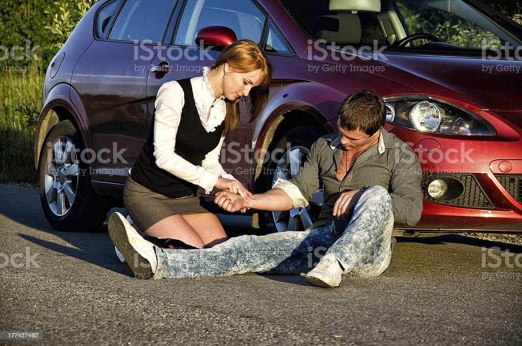 Young girl masures man's pulse on a road. First aid stock photo