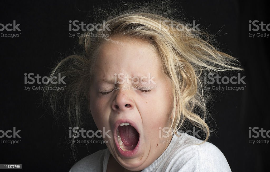Young girl, messy hair, tired and yawning stock photo
