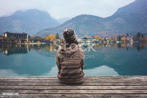 Young Caucasian girl sitting near the lake