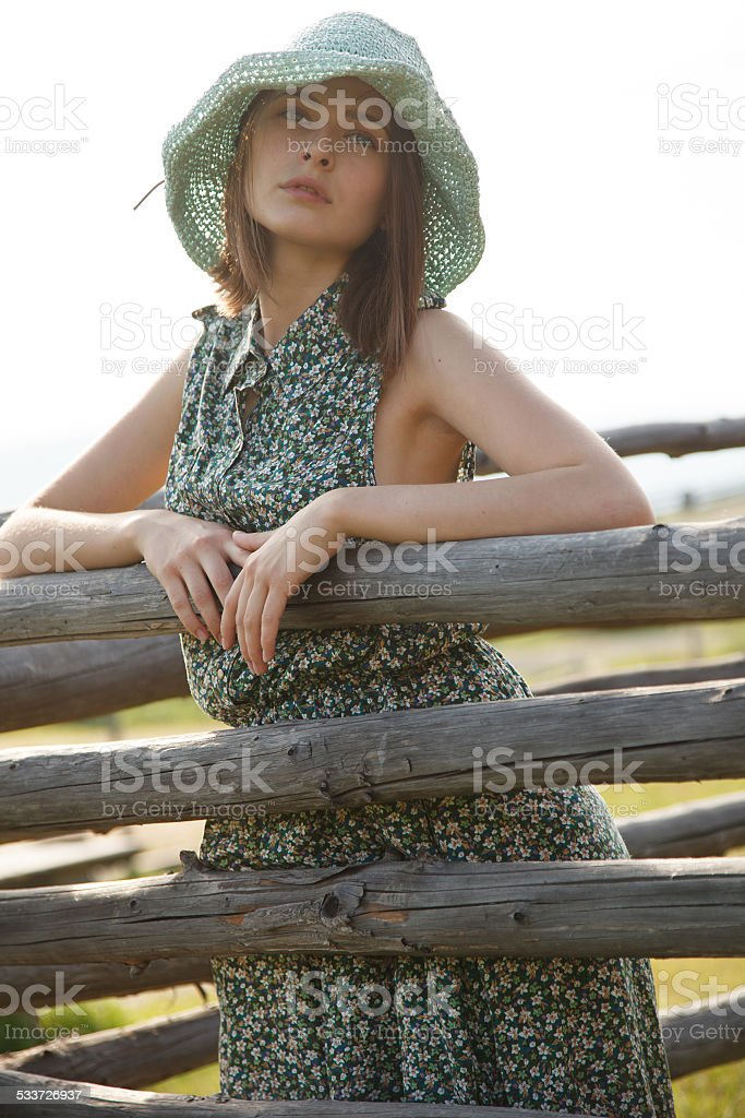 Young girl near wood fence stock photo