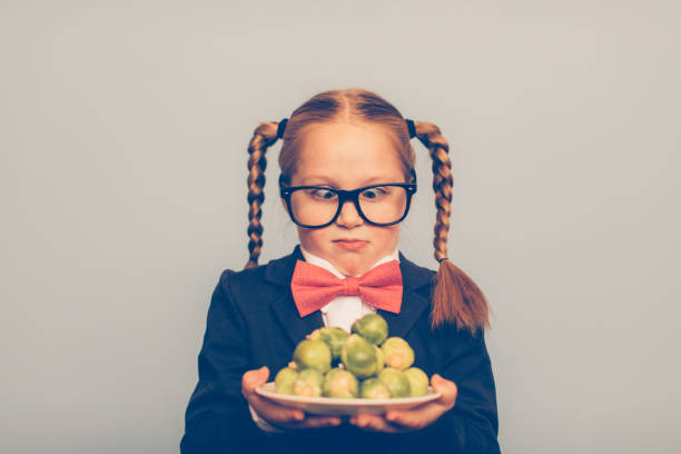 Young Girl Nerd with Brussels Sprouts A young girl nerd wearing eyeglasses, bow tie and cardigan holds a plate of brussels sprout. She is alarmed at the thought of having to eat her vegetables. Holding them and looking at them will not help. nerd hairstyles for girls stock pictures, royalty-free photos & images