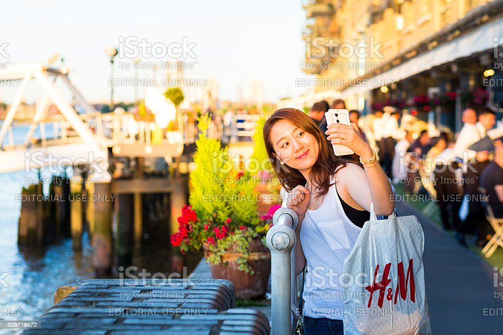 Young girl of Asian ethnicity taking selfie, Southbank, London, UK stock photo