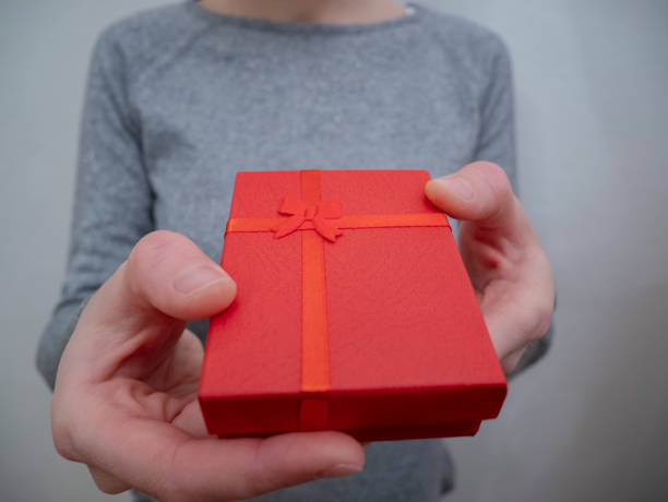A young girl offers a red gift box stock photo