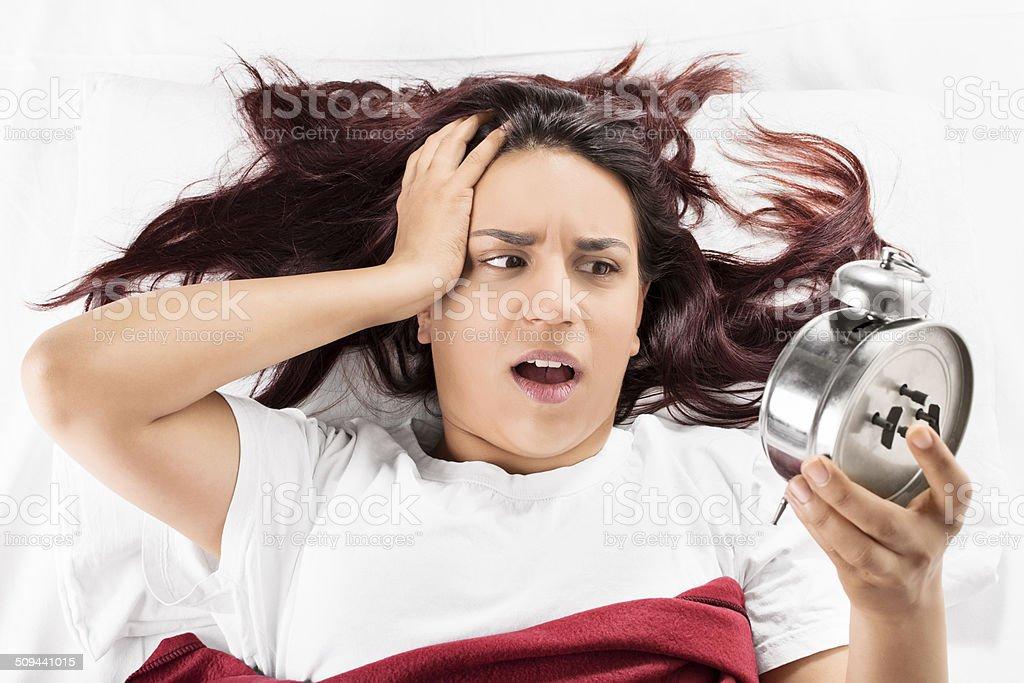 Menina na cama, olhando para o relógio despertador - foto de acervo