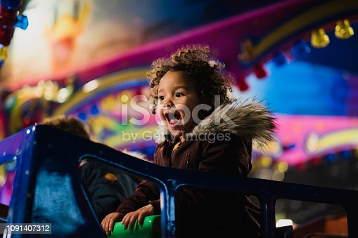A close-up shot of two siblings riding on a carousel, they are having fun together and they are carefree.