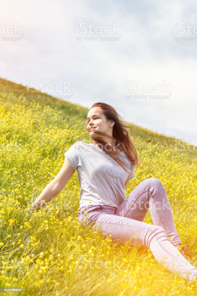 Young girl on a lawn field with yellow flowers royalty-free stock photo