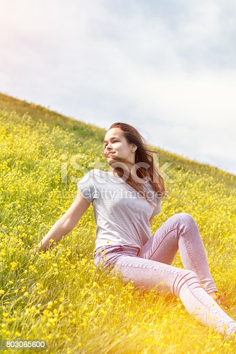 Young Girl On A Lawn Field With Yellow Flowers Stock Photo & More Pictures of Adult