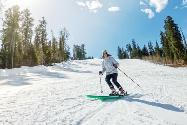 junges mädchen auf alpinen skisport auf einer verschneiten strecke gegen den himmel - winterjacke lang damen stock-fotos und bilder