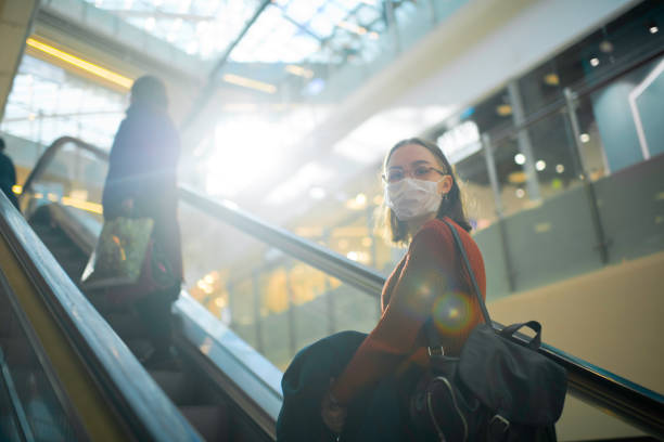 Junges Mädchen auf einer Rolltreppe in Einkaufszentrum mit medizinischer Maske, um sich gegen Virus oder Verschmutzung zu schützen – Foto