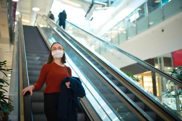 ウイルスや汚染から身を守るために医療マスクを着用したショッピングモールのエスカレーターの若い女の子 - ショッピングセンター ストックフォトと画像