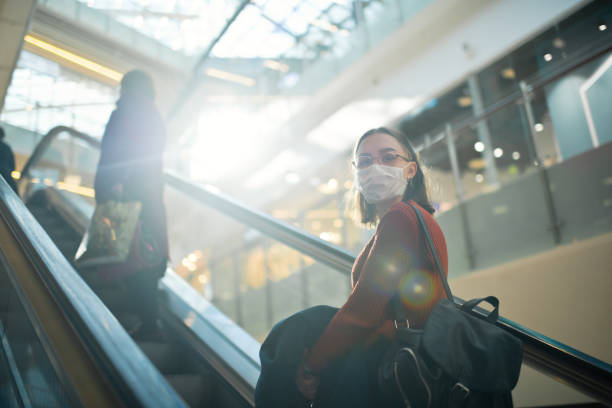 Young girl on an escalator with social distancing in shopping mall wearing medical mask to protect herself against virus