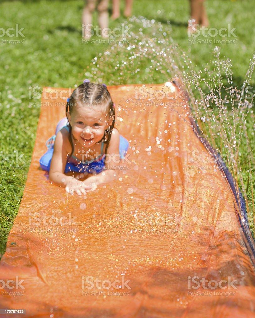 Young girl on Backyard Water Slide stock photo