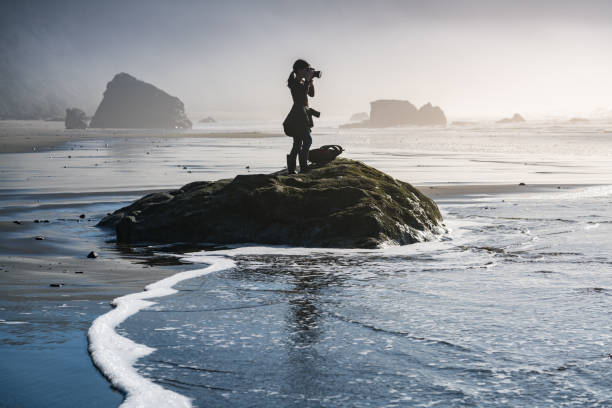 Young girl on beach taking photos of Pacific Ocean in Oregon coast stock photo